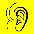 Ear on a yellow background symbol Stock Photos
