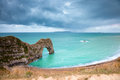 Early morning durdle door swanage dorset england taken as the sun is coming up cloudy sky with rain in the distance Royalty Free Stock Images