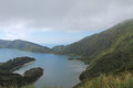 Early morning fog dissipating over lake and green mountains lake in crater and two peninsulas side by side forming a bay são Royalty Free Stock Images