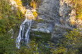 Early morning sun on lucifer fals falls in autumn seen from the overlook in robert h treman state park in trumansburg new york Royalty Free Stock Image