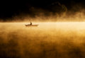 Early morning sunrise, boating on the lake in a huge fog Royalty Free Stock Photo