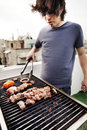 Early s caucasian man busy grilling some meat and vegetables on the roof of a building in urban surroundings Royalty Free Stock Photography