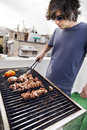 Early s caucasian man busy grilling some meat and vegetables on the roof of a building in urban surroundings Royalty Free Stock Photo