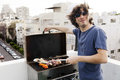 Early s caucasian man giving camera joyful smile standing roof building urban surroundings grilling some meat vegetables wind his Stock Images