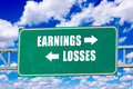 Earnings and losses sign on the green board with clouds in background Stock Photos