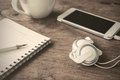 Earphone with coffee and notebook on old wooden table close up of vintage tone Stock Photo