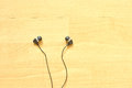 Earphone on wooden background in ear style Stock Images