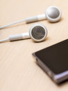 Earphones and mp player on the wooden table Stock Images