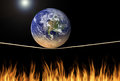 Earth balancing on tightrope over fire environmental climate change message Royalty Free Stock Photo