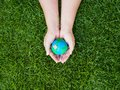 Earth day. earth in hands and green grass field background. envi