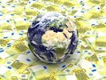 Earth among Euro banknotes Stock Photography