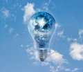 Earth globe and storm in the light bulb on a blue sky vibrant Royalty Free Stock Photo