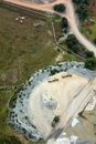 Earth works aerial view of including the mining of sand stone rock and gravel two material carrying trucks await more loads Stock Photo