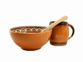 Earthenware crockery soup plate cup and a wooden spoon on a white background Royalty Free Stock Image