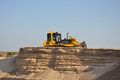 Earthmover bulldozer moves sand at a sand mine Stock Photo