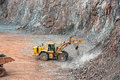 Earthmover in a open pit mine quarry. porphyry rock Royalty Free Stock Photo