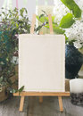 Easel with blank white card. Wedding invitation in retro style