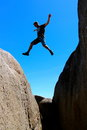East coast tasmania skeleton bay male jumps from rock to rock Stock Photos