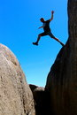 East coast tasmania skeleton bay male jumps from rock to rock Royalty Free Stock Photo