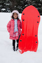 East Indian girl toboganning in the snow Stock Images