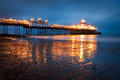 Eastbourne pier at dusk reflecting on a wet sand Royalty Free Stock Images