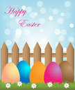 Easter background colorful eggs in a meadow with flowers and a fence Royalty Free Stock Images