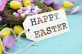 Easter background with painted Easter eggs in birds nest, and yellow and purple silk tulips Royalty Free Stock Photo