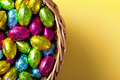 Easter basket chocolate eggs yellow paper background top view macro shot Stock Photography