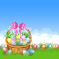Easter basket and colorful Easter eggs in green grass