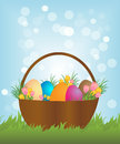 Easter basket with colorful eggs and flowers on a meadow Royalty Free Stock Images