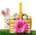 Easter basket with colorful eggs and rabbit on green grass
