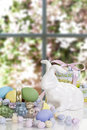 Easter basket rabbit candy a glass filled with eggs and white ceramic behind and decorative boxes and window blurred in background Stock Photos