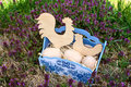 Easter basket with wooden eggs cock and chicken in a blue on a green field Stock Photography