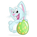 Easter blue bunny with easter colored egg. Vector illustration of a blue rabbit holding Easter colored egg