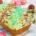 Easter bread kulich with glaze, colorful sugar sprinkles. Colored painted eggs Royalty Free Stock Photo