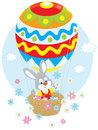 Easter bunny in a balloon little rabbit flies an air colored like an egg and scatters flowers around Royalty Free Stock Photos