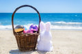 Easter bunny with basket and color eggs on the ocean beach Royalty Free Stock Photo