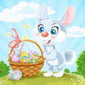 Easter bunny with a basket of eggs on the green la cute lawn Stock Photo