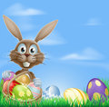Easter bunny and chocolate eggs rabbit in a field with a basket of with copyspace in the sky Stock Photography