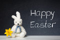 Easter bunny with daffodil before a blackboard sitting Stock Photo