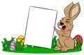 Easter bunny holding a sign in hand Royalty Free Stock Image