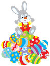 Easter bunny little rabbit sitting on a pile of colorfully painted eggsn Royalty Free Stock Photography
