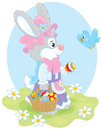 Easter bunny rabbit holding a basket with colorfully decorated eggs Stock Image