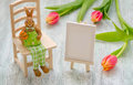 Easter bunny sitting on the stool with a egg, painting easel and tulips over wooden background Royalty Free Stock Photo
