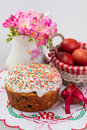 Easter cake jug with flowers and painted eggs on a embroidered napkin Royalty Free Stock Photo
