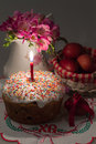 Easter cake with a lit candle flowers and painted eggs jug Stock Photography