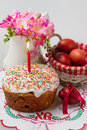 Easter cake with a lit candle jug with flowers and painted eggs on embroidered napkin Royalty Free Stock Photography