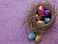 Easter candy a selection of colourful foil wrapped chocolate eggs nestled in a birds nest on sparkly purple background Stock Photo