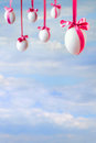 Easter card empty space sky white eggs hanged pink ribbons Royalty Free Stock Images