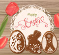 Easter card with lettering and gingerbread in the form of eggs. Tulips background, spring holidays